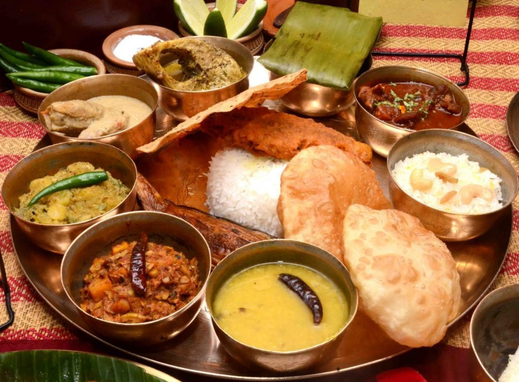 A image of a typical Bengali cuisine. This Bengali thali includes Bhaat, Luchi, Begun Bhaja, Daal, Torkari, Chingri Mach, Sorshe illish, Paturi, Mutton and Payesh.